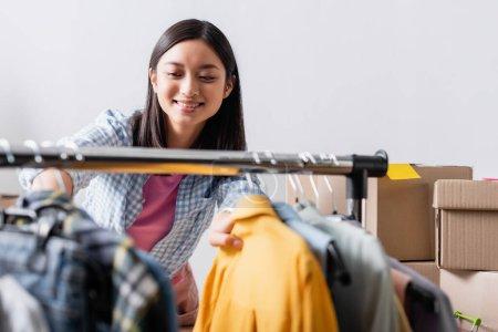 Photo pour Souriant asiatique volontaire debout près de vêtements sur accrocher rack sur flou premier plan - image libre de droit
