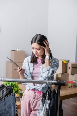 Worried asian volunteer holding clipboard and pen near hanging rack with clothes on blurred foreground