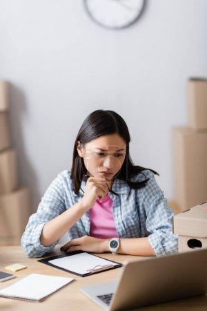 Photo pour Pensive asiatique volontaire tenant stylo et regardant ordinateur portable près de la boîte et presse-papiers sur le premier plan flou - image libre de droit