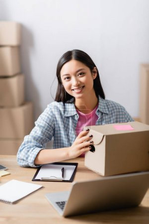 Photo for Asian volunteer looking at camera while holding box near clipboard and laptop on blurred foreground - Royalty Free Image