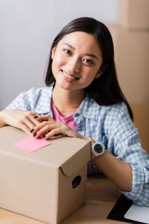 Photo pour Sourire femme asiatique regardant caméra près de la boîte avec note collante dans le centre de charité - image libre de droit