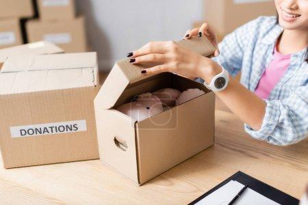 Ausgeschnittene Ansicht einer lächelnden freiwilligen Aufbewahrungsbox mit Plüschtier in der Nähe des Pakets mit Spendenaufdruck und Klemmbrett auf dem Tisch