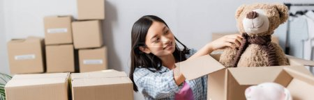 Positive asian volunteer putting soft toy in box near packages on blurred foreground, banner