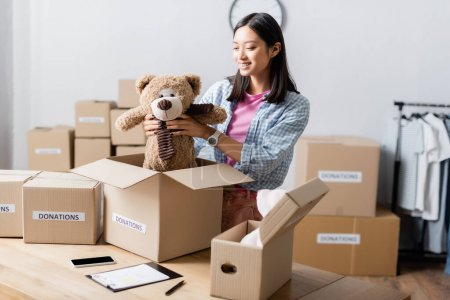 Photo for Asian volunteer holding soft toy near boxes with donations lettering, clipboard and smartphone in charity center - Royalty Free Image