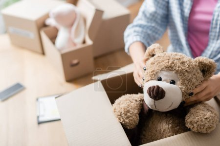Cropped view of volunteer putting soft toy in carton package in charity center