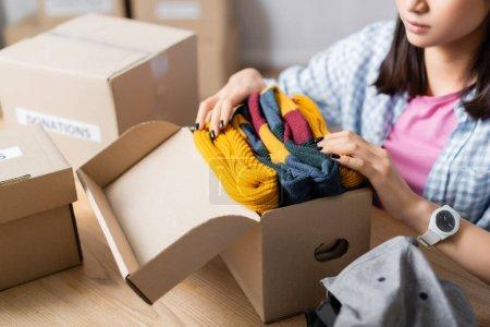 Ausgeschnittene Ansicht von Freiwilligen, die Kleidung in Pakete in der Nähe von Boxen in Charity-Zentrum legen