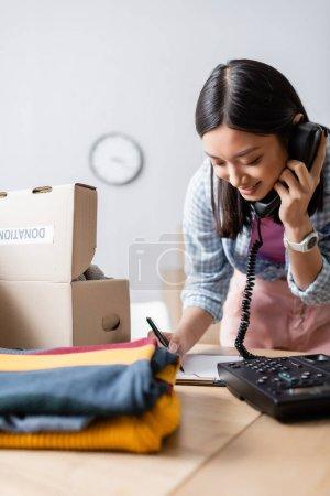Photo pour Souriant asiatique bénévole écriture sur presse-papiers tout en parlant au téléphone près de la boîte avec don lettrage et vêtements sur flou au premier plan - image libre de droit