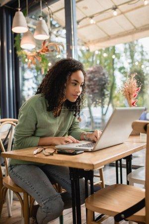 Photo pour Focalisé femme afro-américaine en utilisant un ordinateur portable dans le café - image libre de droit