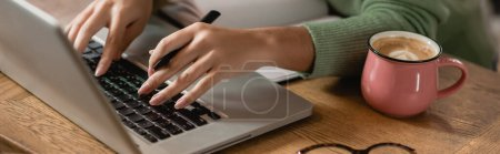 Photo for Partial view of african american woman holding pen while typing on laptop keyboard, banner - Royalty Free Image