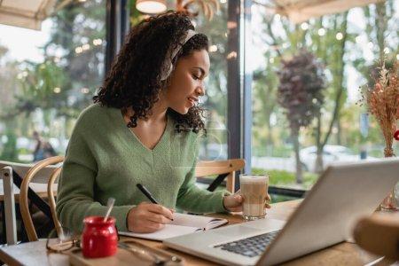 Photo pour Afro-américaine femme écoute podcast dans les écouteurs et tenant verre avec café près ordinateur portable dans le café - image libre de droit