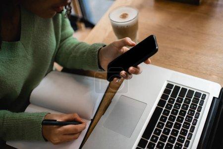 Ausgeschnittene Ansicht einer Afroamerikanerin mit Smartphone und leerem Bildschirm in der Nähe von Laptop und Notebook