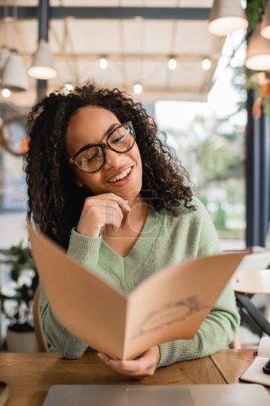 feliz rizado africano americano mujer en gafas celebración menú en borrosa primer plano