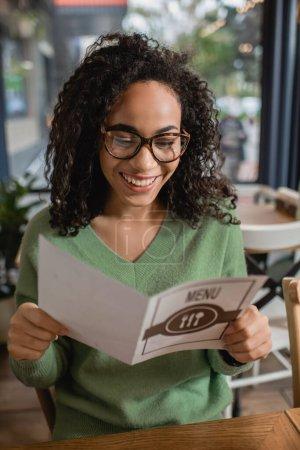 Photo pour Joyeuse femme afro-américaine bouclée dans des lunettes tenant le menu au premier plan flou - image libre de droit