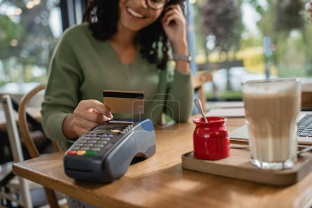 cropped view of happy african american woman holding credit card above payment terminal in cafe