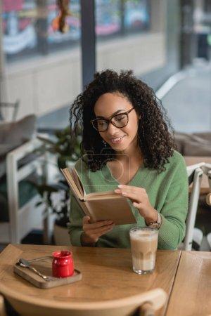 glücklich afrikanisch-amerikanische Frau in Brille Lesebuch neben Glas mit Latte