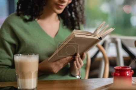 partial view of african american woman reading book near glass with latte on blurred foreground