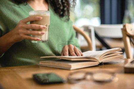 Photo pour Vue recadrée de femme afro-américaine tenant verre avec latte tout en lisant le livre dans le café - image libre de droit