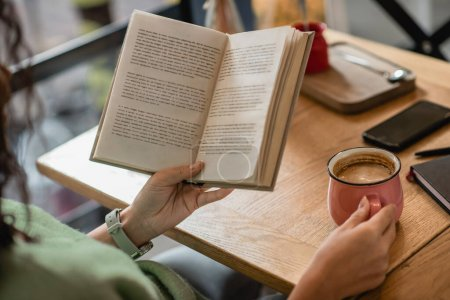 partial view of african american woman holding book and cup of cappuccino in cafe