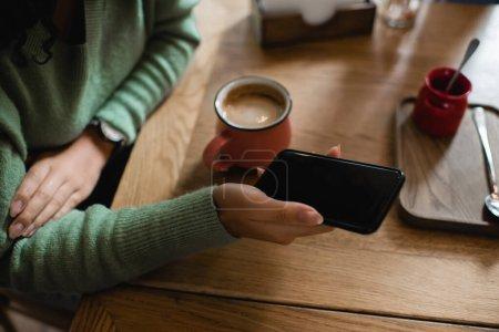 Photo pour Vue partielle de la femme afro-américaine tenant smartphone avec écran vide près de tasse de cappuccino - image libre de droit