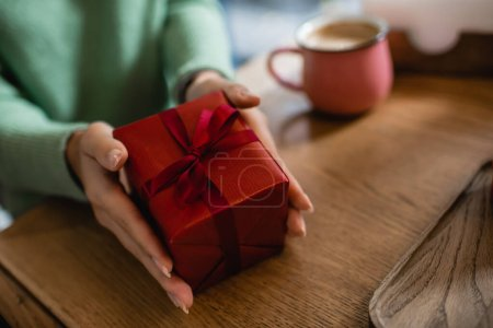 cropped view of african american woman holding wrapped christmas gift in cafe