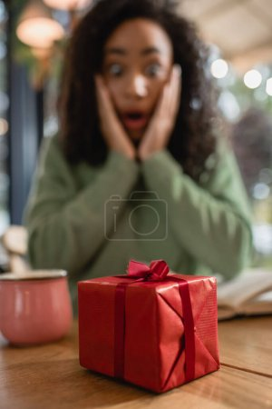 red christmas gift box near shocked african american woman on blurred background