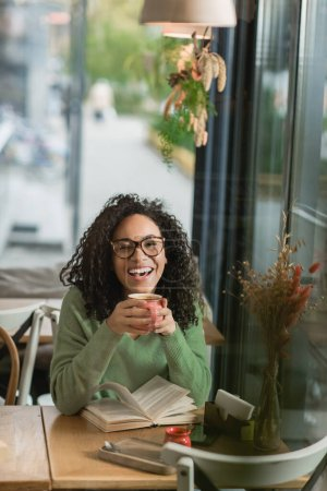 amazed african american woman in eyeglasses holding cup of coffee near book on table in cafe