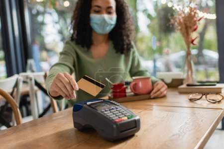 credit card near credit card reader in hand of african american woman in medical mask on blurred background