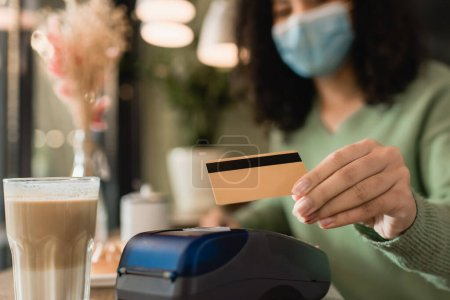 glass of latte near credit card in hand of african american woman in medical mask paying on blurred background