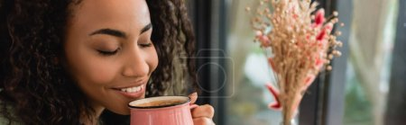 Photo for Pleased african american woman holding pink cup with coffee in cafe, banner - Royalty Free Image