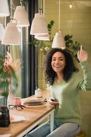 cheerful african american woman gesturing while asking for bill in cafe