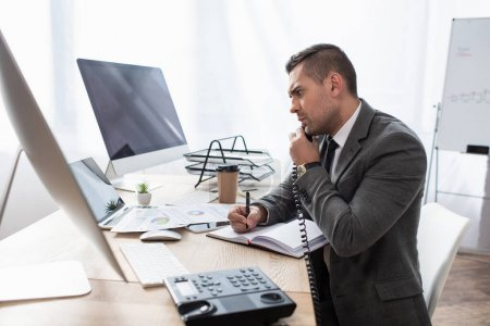 Photo for Serious trader talking on telephone while writing in notebook near computer monitors and notebook, blurred foreground - Royalty Free Image