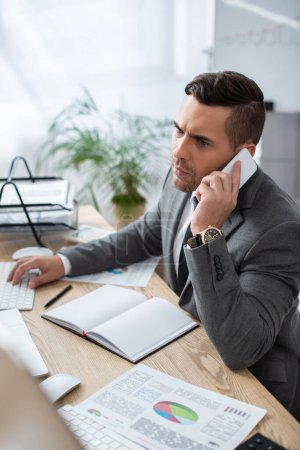 Photo for Serious businessman talking on smartphone near notebook and infographics in office, blurred foreground - Royalty Free Image