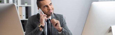 Photo pour Homme d'affaires souriant et rêveur regardant ailleurs tout en parlant sur smartphone et en tenant un stylo, premier plan flou, bannière - image libre de droit
