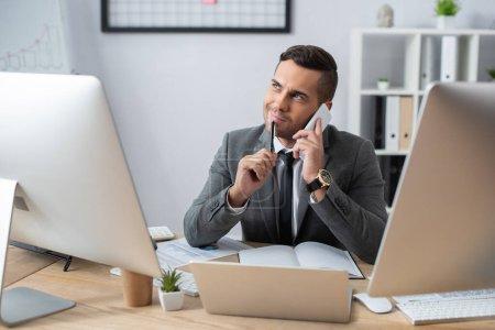 Foto de Comerciante sonriente mirando hacia otro lado mientras habla en el teléfono móvil cerca de la computadora portátil y monitores en el lugar de trabajo - Imagen libre de derechos