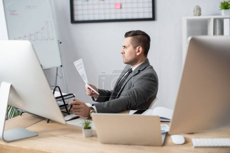 Photo for Side view of businessman looking at document near laptop and monitors - Royalty Free Image