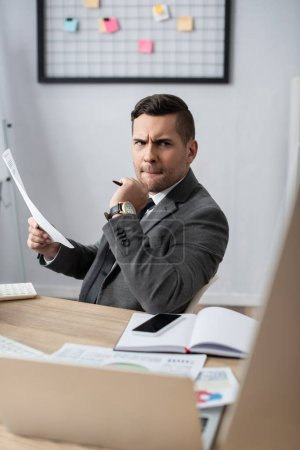 Photo for Thoughtful trader holding paper near notebook, smartphone and laptop on blurred foreground - Royalty Free Image