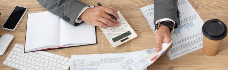 Photo for Partial view of trader working with calculator and infographics near notebook and coffee to go, banner - Royalty Free Image