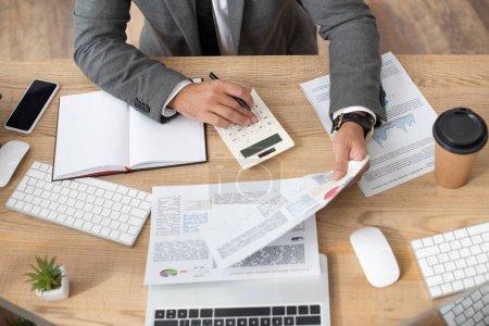 Photo pour Vue partielle du trader travaillant avec l'infographie et la calculatrice près du smartphone et des claviers - image libre de droit