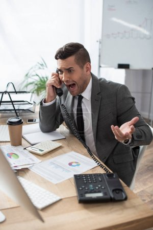 Photo for Angry trader screaming while talking on landline phone near papers with infographics, blurred foreground - Royalty Free Image