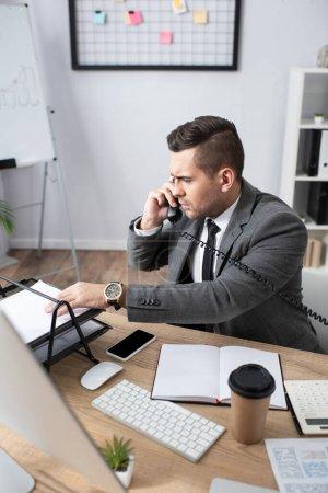 Photo pour Sérieux commerçant prenant du papier tout en parlant au téléphone près de smartphone et ordinateur portable, flou premier plan - image libre de droit