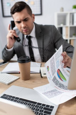 businessman talking on landline phone while looking at papers with infographics, blurred background