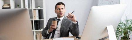 Photo pour Commerçant réfléchi tenant café pour aller et stylo près des moniteurs d'ordinateur, bannière - image libre de droit