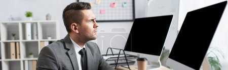 serious trader looking at monitors with blank screen in office, banner