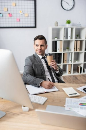 Photo for Smiling trader holding coffee to go while writing in notebook near computer monitor on blurred foreground - Royalty Free Image