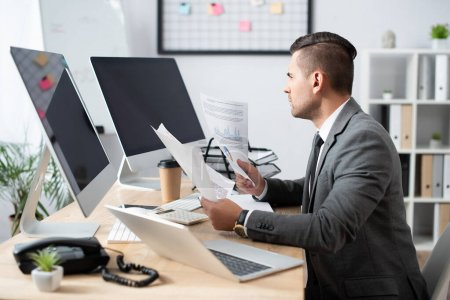 Photo for Businessman holding infographics while sitting at workplace near monitors with blank screen, blurred foreground - Royalty Free Image
