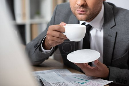 Photo for Cropped view of trader holding coffee cup at workplace, blurred foreground - Royalty Free Image