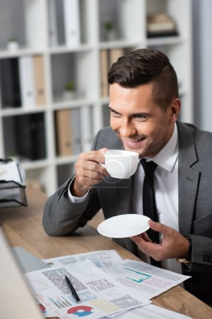 smiling businessman holding coffee cup at workplace near infographics, blurred foreground