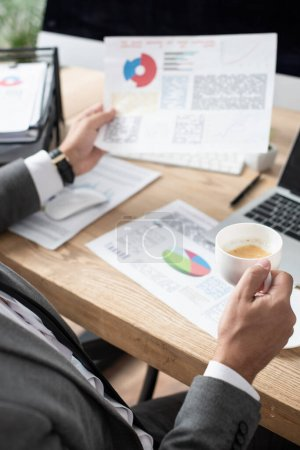 cropped view of trader holding coffee cup and infographics, blurred background