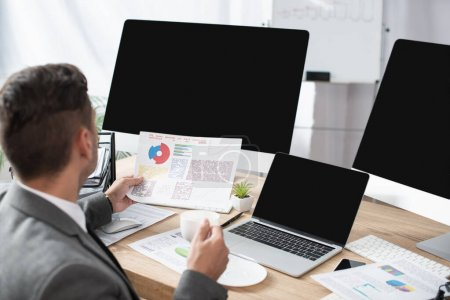 trader holding infographics near laptop and monitors with blank screen, blurred foreground