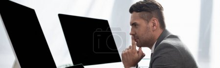 Photo for Side view of concentrated trader near monitors with blank screen, banner - Royalty Free Image